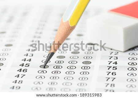 Filled answer sheet with eraser focus on pencil - stock photo
