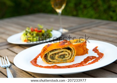 filled pasta with salad and wine  - stock photo
