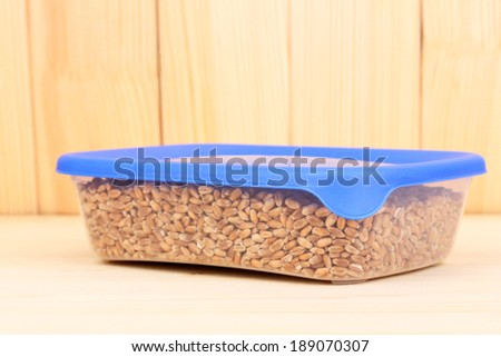 Filled plastic container on wooden background - stock photo