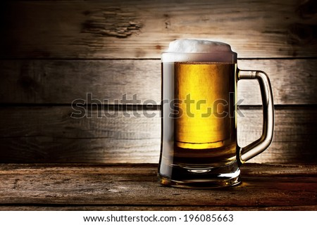 Filled with beer glass with white foam on background of wooden planks - stock photo