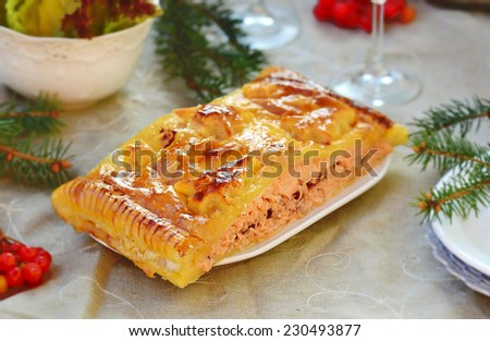 fillet of a salmon in puff pastry on a New Year's holiday table. selective focus - stock photo