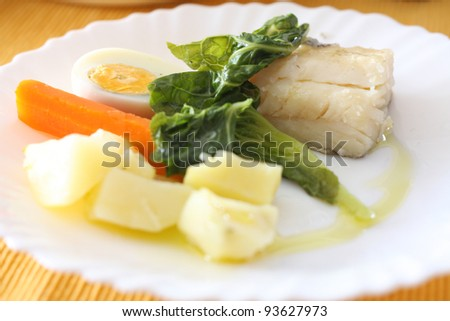 fillet of baked cod with egg and vegetables - stock photo