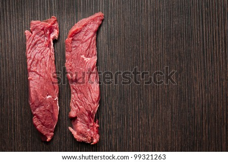 Fillet raw meat on cutting board - stock photo