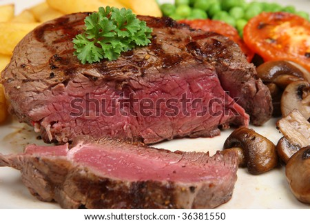 Fillet steak with peas, chips, mushrooms and tomato - stock photo