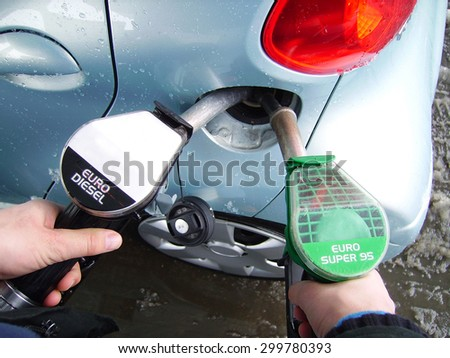 Filling car tank with two nozzles, different fuel - stock photo