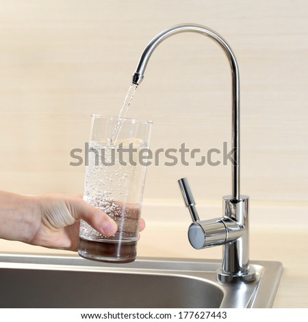 Filling glass of water from kitchen faucet - stock photo
