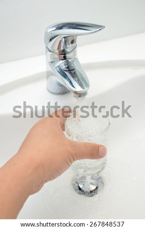 Filling glass of water from stainless steel faucet - stock photo