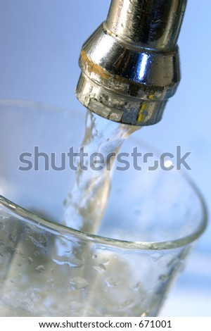 filling glass with water - stock photo