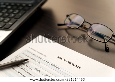 Filling Health insurance form on a wooden table - stock photo