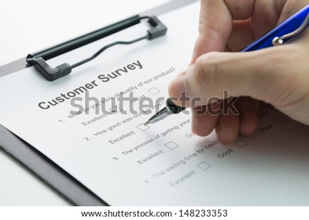Filling in customer satisfaction survey form with pen - stock photo