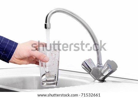 filling in glass of drink  water from faucet - stock photo
