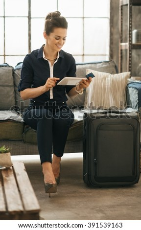 Filling inspired for adventure! Smiling elegant woman with credit card and ready for departure luggage ordering ticket online with tablet PC while sitting on sofa in loft apartment. - stock photo