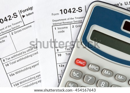 Filling out the form 1042-s which confirms the payment of the tax in the United States - stock photo