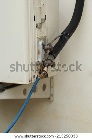 filling refrigerant to air conditioner drip valve - stock photo