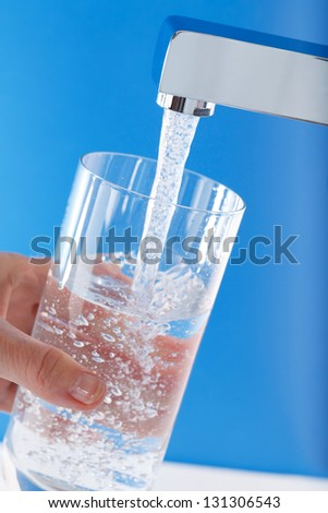 Filling up a glass of water . Blue background. - stock photo