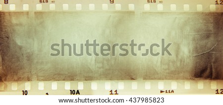 Film negative frames on brown paper - stock photo
