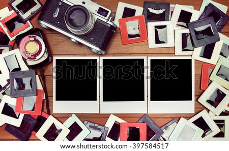 Film photos on the table. retro camera and some old photos on wooden table. Vintage look - stock photo