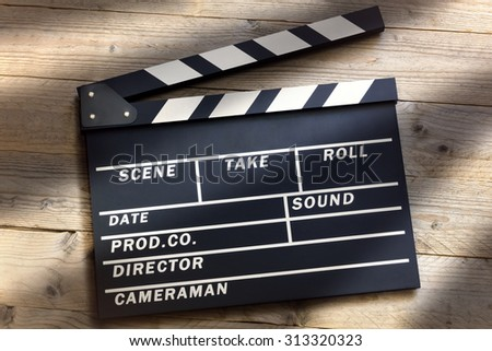 Film slate or movie clapper board on wood background - stock photo