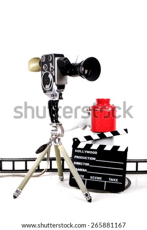 Film strip with clapperboard and vintage camera over white. - stock photo