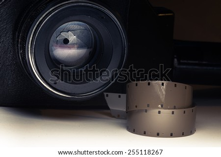 Film strips closeup with vintage movie cinema camera in shadow on background - stock photo