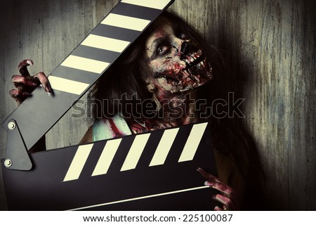Filming a horror movie. Female zombie holding clapper board. Cinematography. Halloween. - stock photo