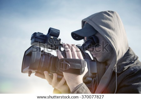 Filmmaking. Men with High Definition Modern Video Camera Shooting Some Video. - stock photo