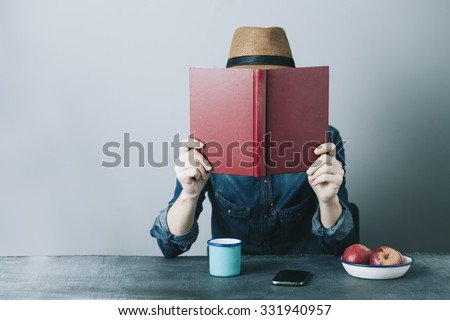 filtered photo of a young hipster man reading a book and relaxing - stock photo
