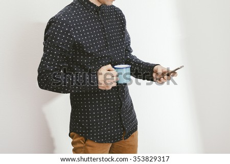 filtered photo of a young stylish man holding a coffee and a smartphone - stock photo