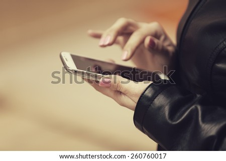 filtered photo of an young woman holding a smart phone and touching the screen with her finger - stock photo