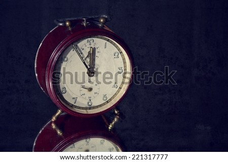 Filtered picture of a vintage alarm clock on a mirror background - stock photo