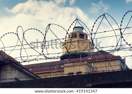 Filtered vintage guarding tower behind barbed wire fence prison walls - stock photo