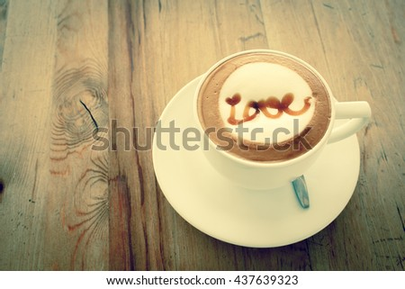 Filtered vintage tone A Latte Coffee art on the wooden desk.A cup of coffee with love word. - stock photo