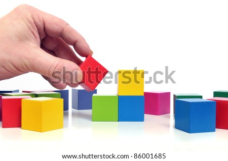 Final step to success - Human hand and multicolored toy blocks on white background - stock photo
