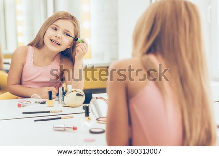 Final touch. Cheerful little girl applying mascara and looking at her reflection in mirror while sitting at the dressing table - stock photo