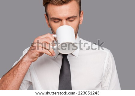 Finally coffee break . Tired young man in formalwear holding coffee cup and drinking it while standing against grey background - stock photo