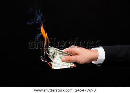 finances, people, savings and bankruptcy concept - close up of male hand holding burning dollar cash money over black background - stock photo