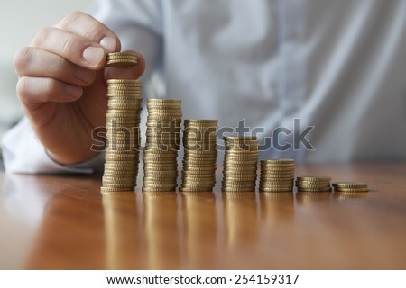 Finances, Person stacking Euro coins, close-up - stock photo
