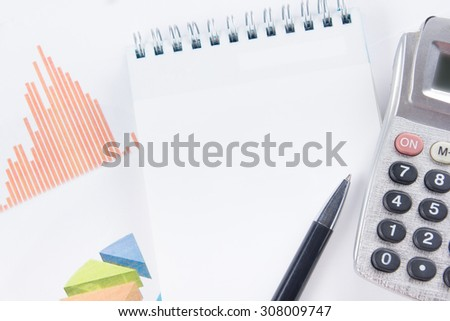 Financial accounting stock market graphs analysis. Calculator, notebook with blank sheet of paper, pen on chart. Top view - stock photo