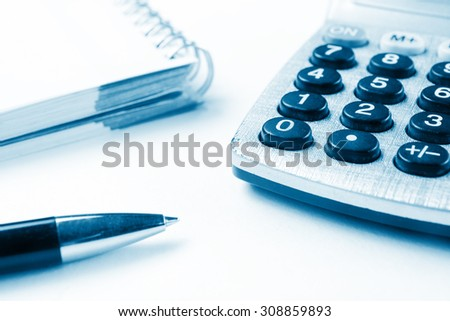 Financial accounting stock market graphs analysis. Close-up shot of calculator, notebook with blank sheet of paper, pen on chart. Blue toned - stock photo