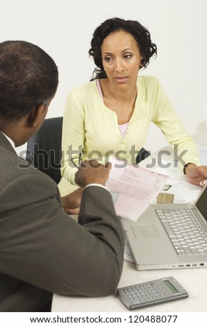 Financial adviser in discussion with woman a desk in office - stock photo