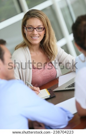 Financial adviser meeting with couple in office - stock photo