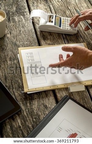 Financial adviser or accountant checking statistical data and numbers while making calculations using desk calculator. - stock photo