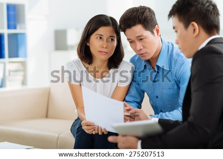 Financial adviser showing mortgage application form to the family - stock photo