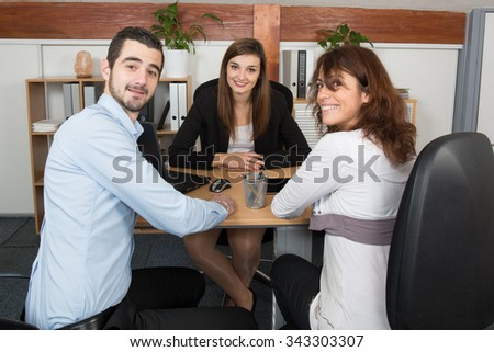 Financial advisor or lawyer giving advice to happy and lovely couple - stock photo