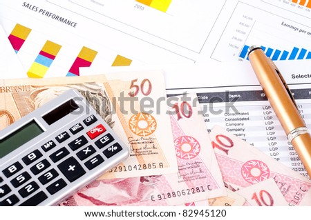 Financial analysis with the graph and data of industrial growth. Brazilian money, pen and calculator. - stock photo