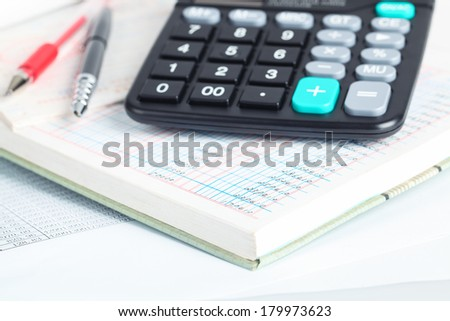financial books closeup with calculator and pen - stock photo