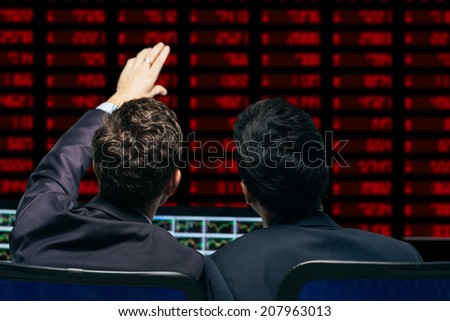 Financial brokers discussing stock market quotes, rear view - stock photo