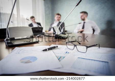 financial chart near dollars seen by unfocused glasses ( colleagues meeting to discuss their future financial plans only silhouettes being viewed )  - stock photo
