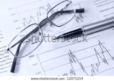 Financial chart pen and glasses. - stock photo
