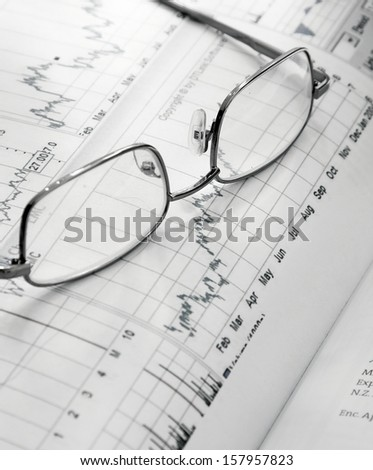 Financial charts and glasses - stock photo